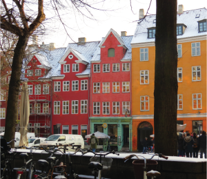 A quiet plaza in Copenhagen, Denmark, offers a scenic view of colorfully painted buildings.