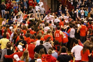 Fans swamp the players after waiting for the opponents from Marietta College to leave the court.