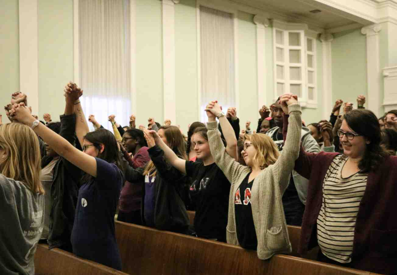 Students stand with their fists raised in solidarity with the victims of sexual assault in Allison Hall.