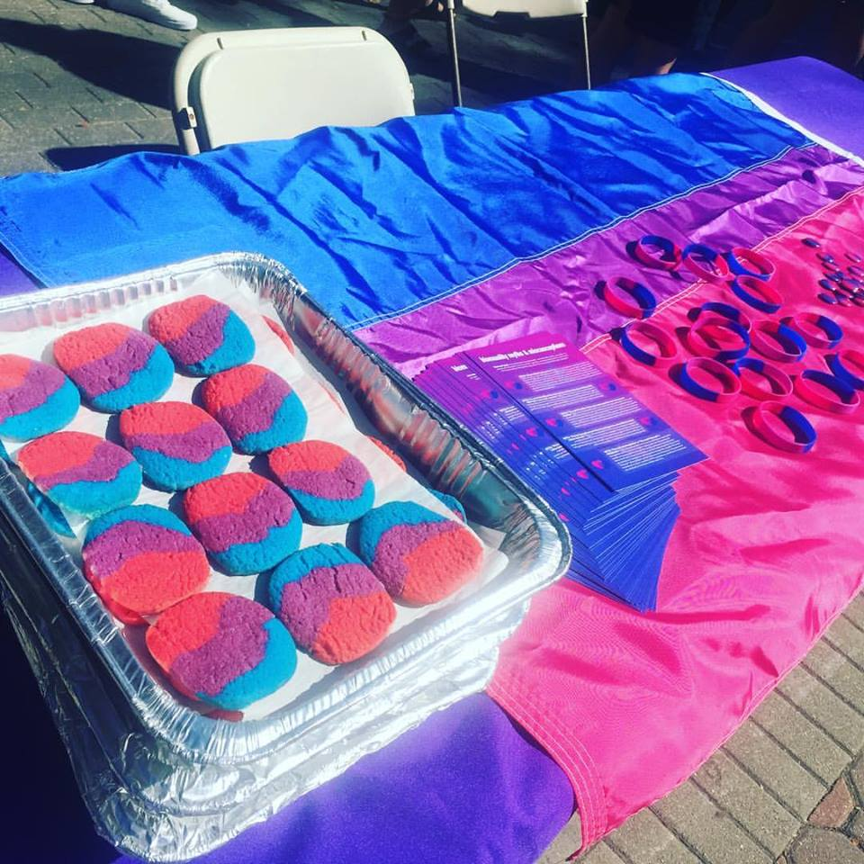 The table at then event had cookies, bracelets, and pamphlets sporting the blue, pink, and purple colors of the bisexuality pride flag.