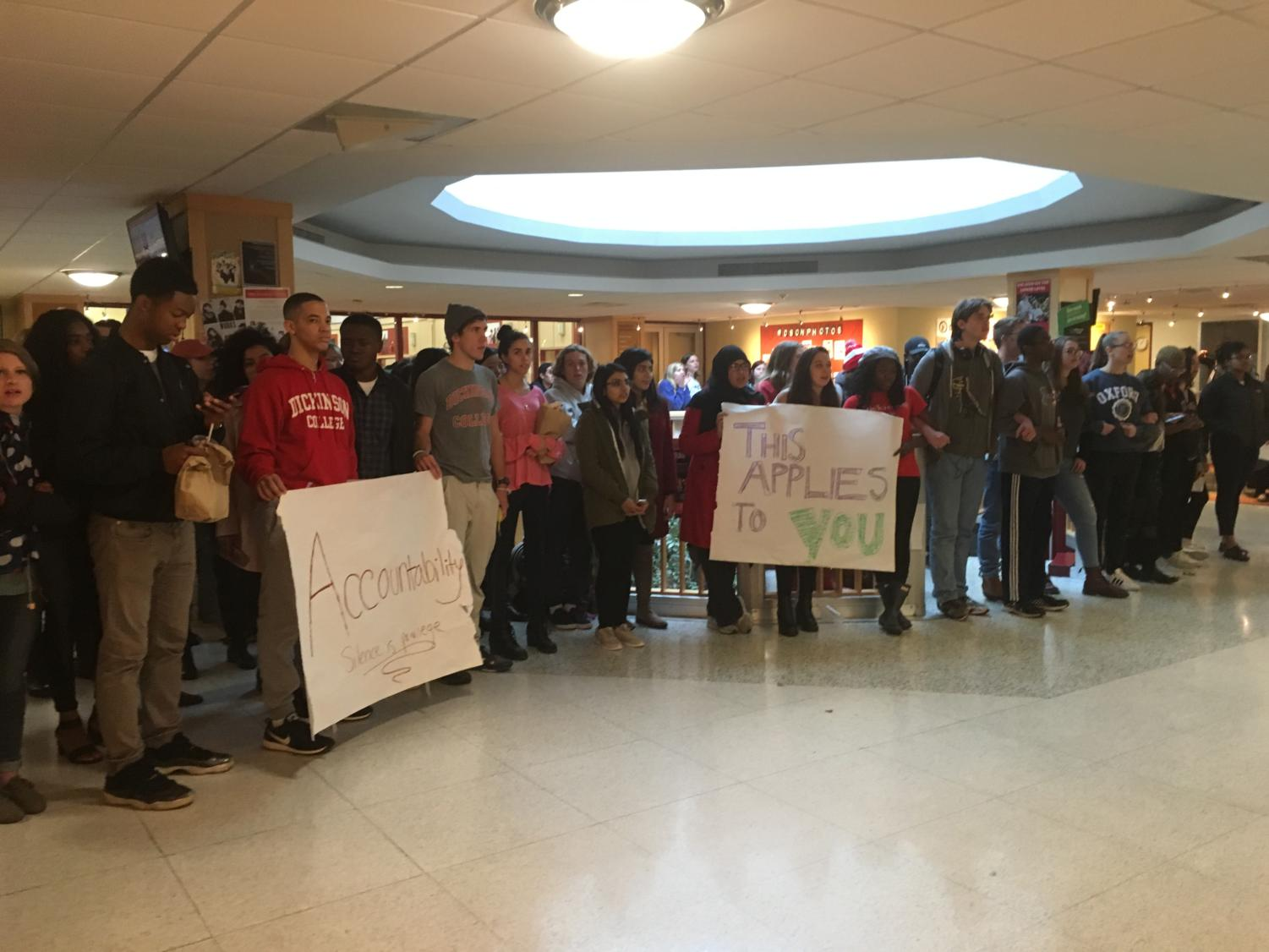 Students held signs and linked arms outside of the Tuesday, Nov. 7 faculty meeting from 12 p.m. to 12:40 p.m., then moved the protest to the HUB stairwell.